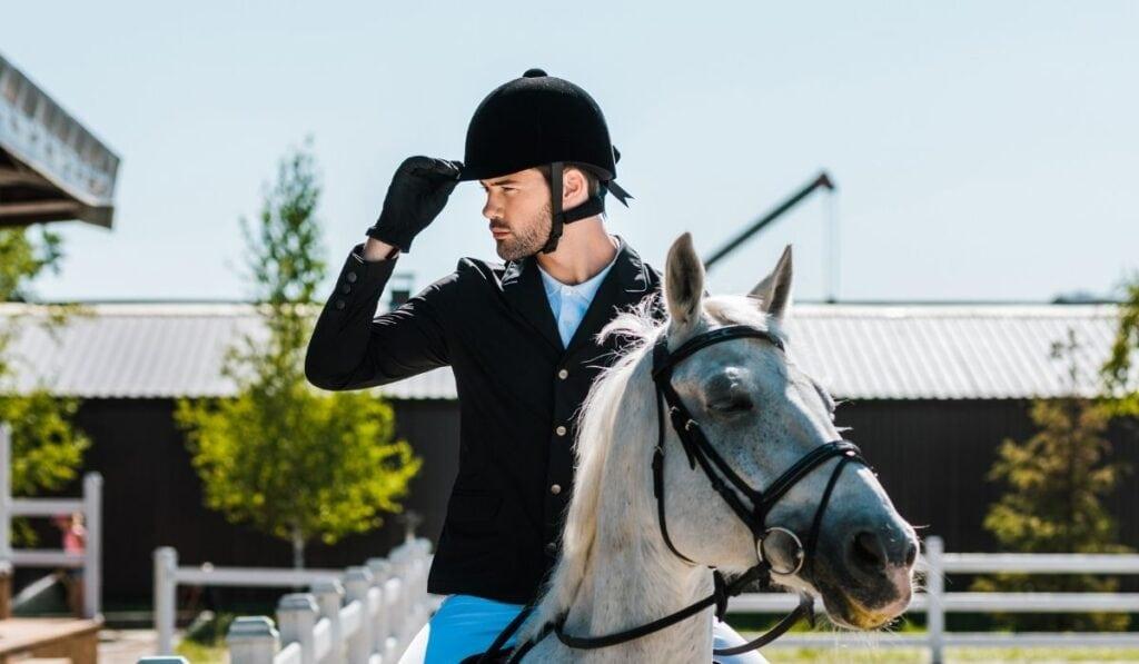 Equestrian riding horse touching riding helmet